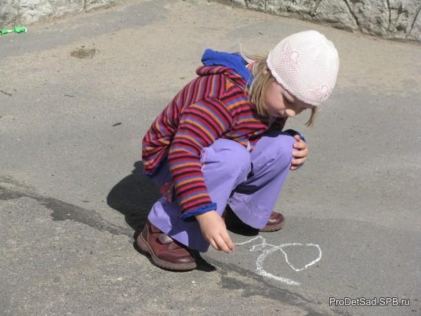 ребенок рисует на асфальте