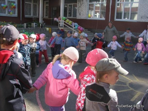 дети водят хоровод на улице летом