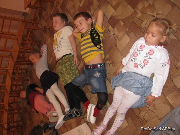 дети лежат на ковре и слушают музыку