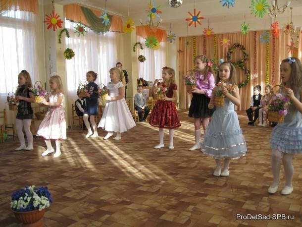 Девочки танцуют танец с цветами.
